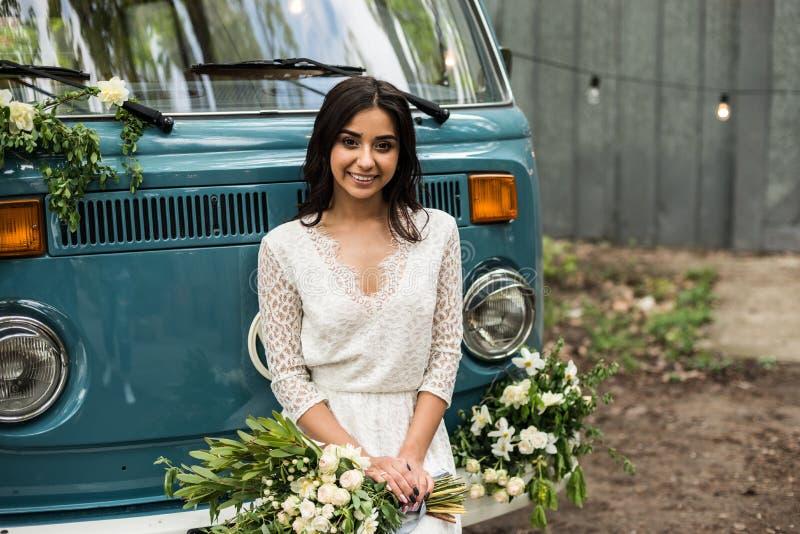 Rozochocona szczęśliwa młoda panna młoda siedzi na rekordowym minibusie Zakończenie obraz stock