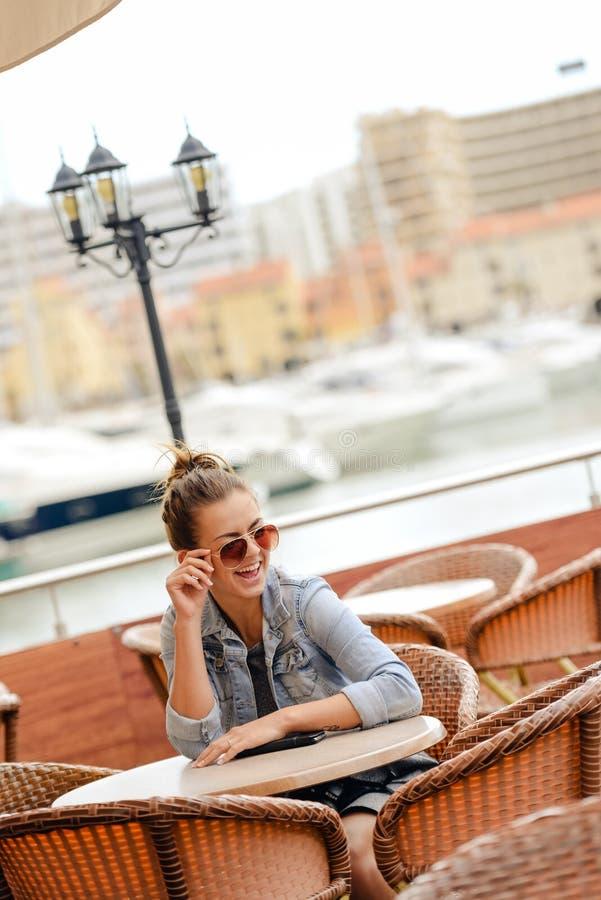 Rozochocona szczęśliwa uśmiechnięta ładna kobieta w restauraci na luksusowym marina tle fotografia royalty free