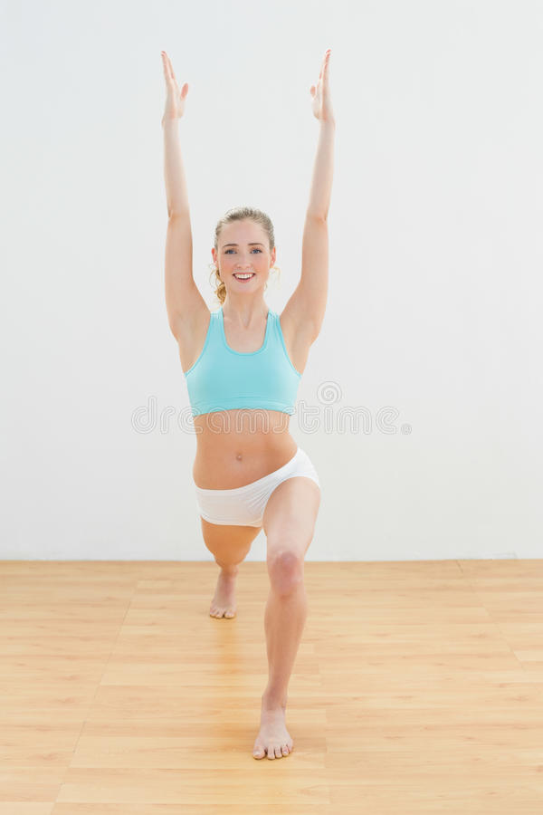 Rozochocona szczupła blondynki pozycja w wysokiej lunge pozie fotografia stock