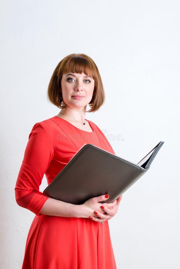 Rozochocona ufna biznesowej kobiety pozycja w białej biurowej izbowej mienie falcówce dla papierów obrazy stock