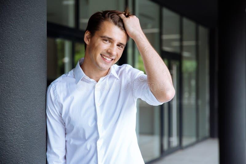 Rozochocona ufna młoda biznesmen pozycja, ono uśmiecha się i zdjęcia royalty free