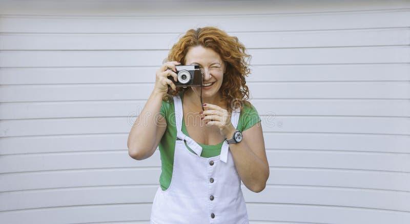 Rozochocona w średnim wieku dama używa rocznik kamerę Dzień, plenerowy Szczęśliwa czerwona włosiana kobieta bierze obrazek na ret zdjęcie royalty free