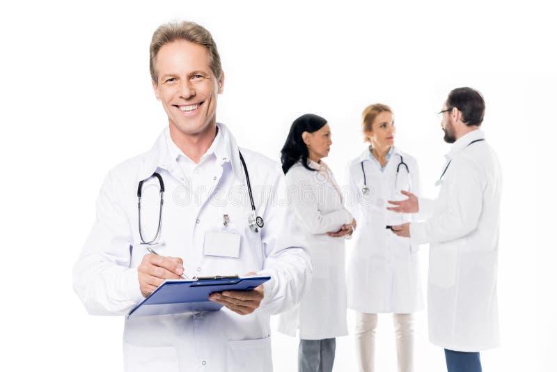 rozochocona w średnim wieku lekarka patrzeje kamerę z stetoskopem i schowkiem podczas gdy koledzy stoi behind obrazy stock