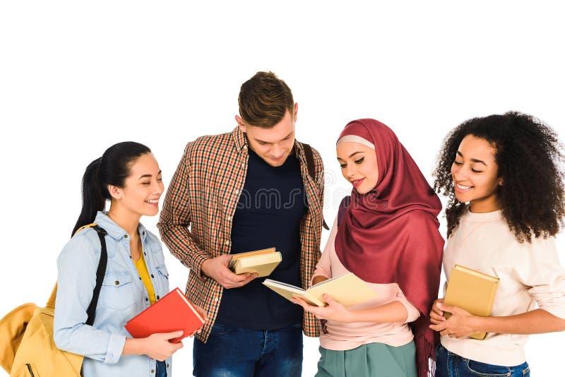 rozochocona wieloetniczna grupa młodzi ludzie czytelniczej książki odizolowywającej zdjęcie royalty free