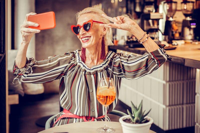 Rozochocona z włosami starsza dama pozuje z szerokim uśmiechem fotografia stock