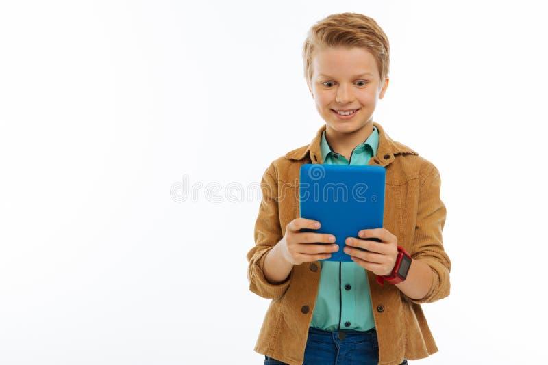 Rozochocona zadowolona chłopiec patrzeje pastylka ekran zdjęcie stock