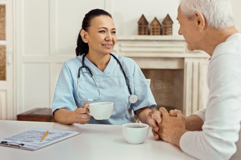 Rozochocona zadowolona pielęgniarka trzyma filiżankę herbata zdjęcie royalty free