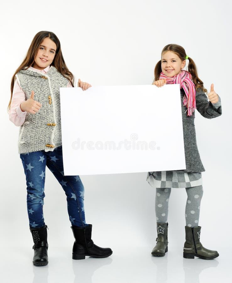 Rozochocone dziewczyny trzyma puste miejsce deskę obrazy stock