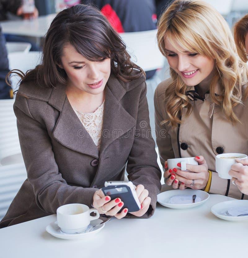 Rozochocone kobiety bawić się telefon komórkowego zdjęcie stock