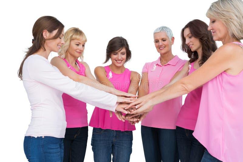 Rozochocone kobiety pozuje w okręgu jest ubranym menchie dla nowotworu piersi obraz stock