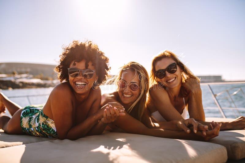 Rozochocone kobiety sunbathing na intymnym jachcie zdjęcie royalty free