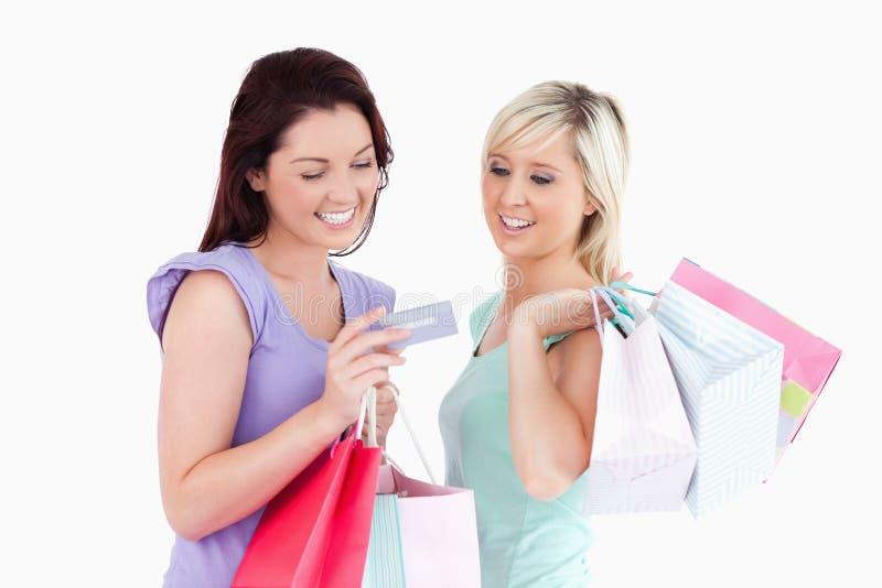 Rozochocone kobiety z torba na zakupy i kartą zdjęcie stock