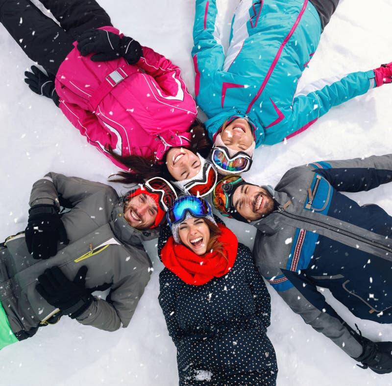 Rozochocone narciarki kłama na śniegu i ma zabawa odgórnego widok obrazy royalty free