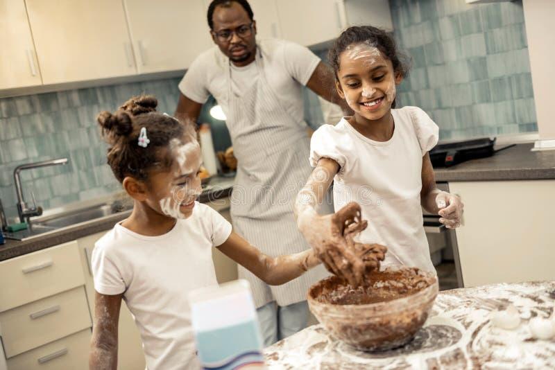 Rozochocone piękne córki czuje zadziwiające kulinarne babeczki zdjęcia stock