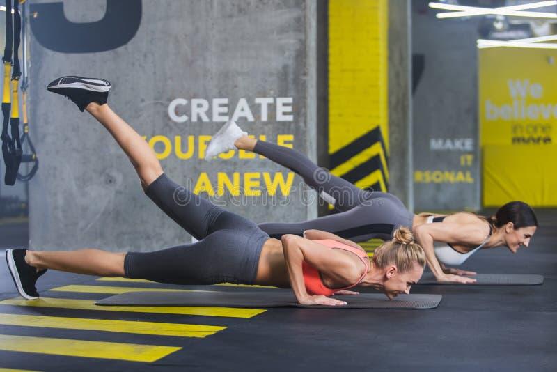 Rozochocone sporty damy robią Ups w gym obraz royalty free