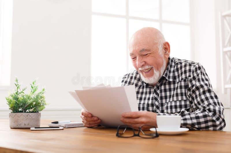 Rozochocone starszego mężczyzna przyglądające fotografie, kopii przestrzeń obraz royalty free