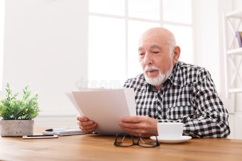 Rozochocone starszego mężczyzna przyglądające fotografie, kopii przestrzeń fotografia stock