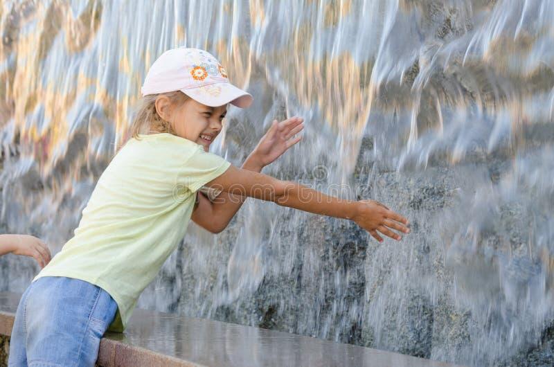 Rozochocone sześć rok dziewczyn w lat ubraniach wręcza próbować dostawać wodną sztuczną siklawę zdjęcia royalty free