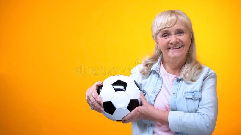 Rozochoconego emeryt kobiety mienia futbolowa pi?ka, sporty zak?ada si?, pozytywna postawa zdjęcie stock