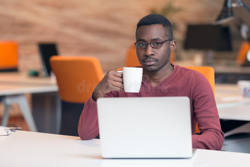 Rozochoconego młodego Afrykańskiego biznesmena pisać na maszynie patrzeć na laptopie obrazy stock