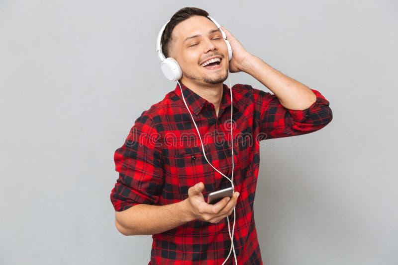 Rozochoconego młodego człowieka słuchająca muzyka z hełmofonami obraz stock