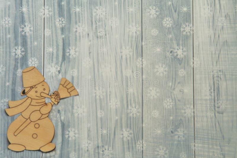 Rozochoconego rocznika drewniany bałwan z miotłą na lekkim tle dekorował z płatek śniegu zdjęcie stock