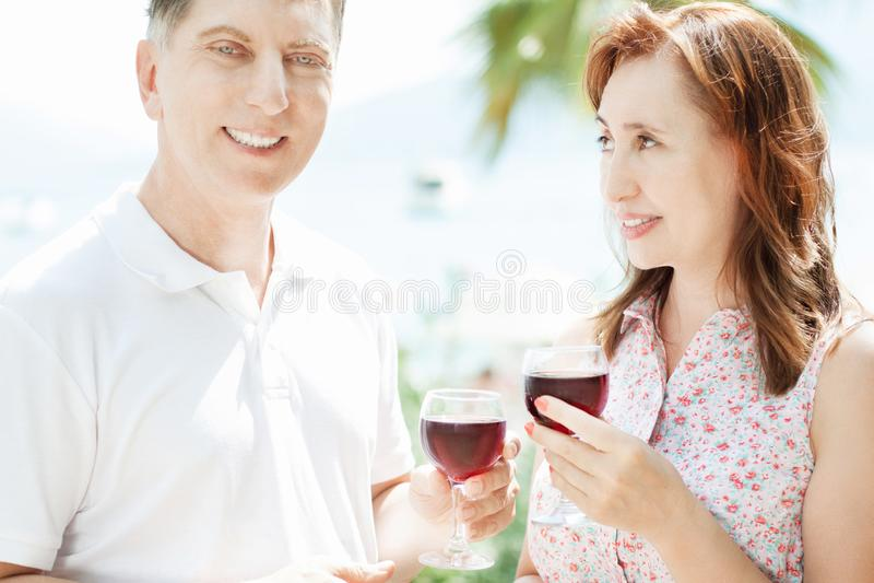 Rozochoconego uśmiechu pary mienia czerwonego wina w średnim wieku szkła i pozycja blisko dennym tłem - lata pojęcia ludzie zdjęcie stock