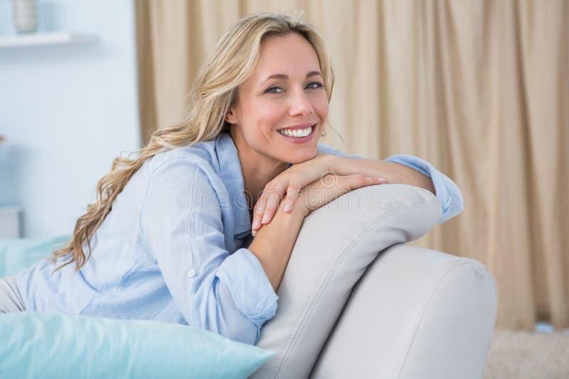 Rozochocony ładny blondynki obsiadanie na leżance fotografia stock