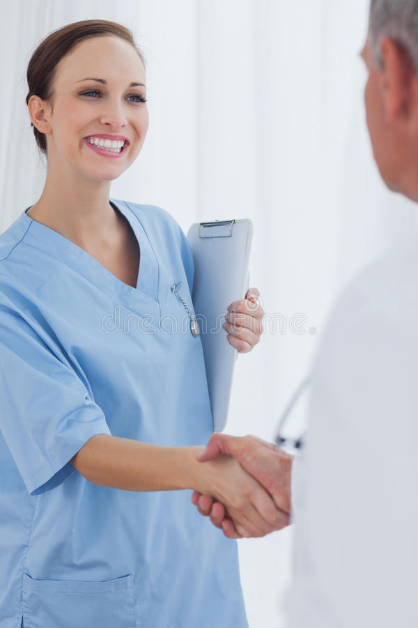 Rozochocony ładny chirurg wita jej nowego workmate zdjęcie royalty free