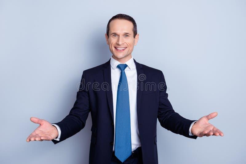 Rozochocony, ładny mężczyzna w formalnej odzieży z krawatem ma jego ręki, otwiera zdjęcia royalty free