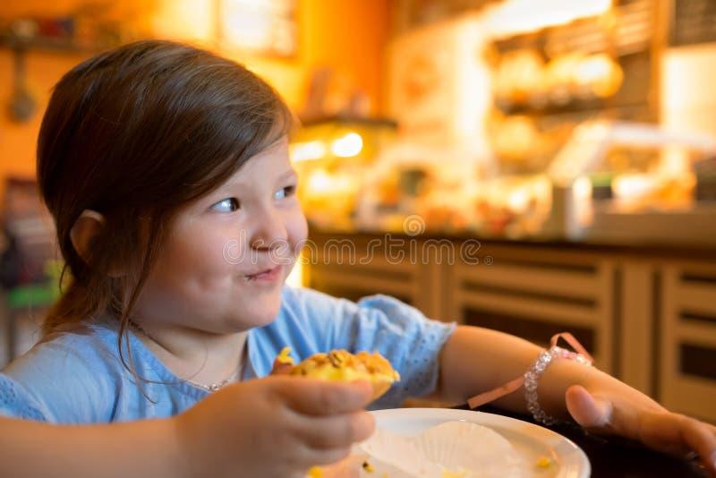 Rozochocony ładny małej dziewczynki obsiadanie przy stołem podczas gdy jedzący cukierki tort fotografia stock