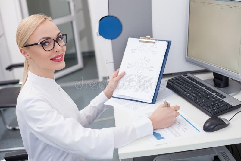 Rozochocony żeński badacz robi niektóre notatkom fotografia stock