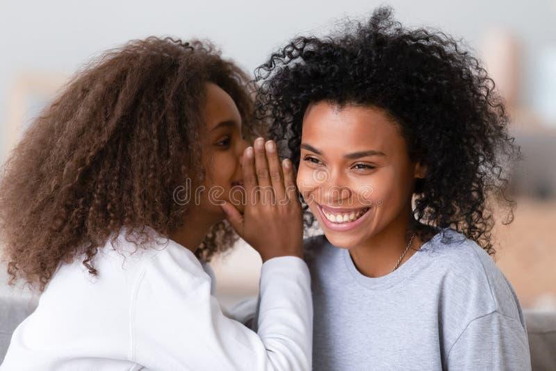 Rozochocony afrykański córka szept matka ucho sekret fotografia royalty free