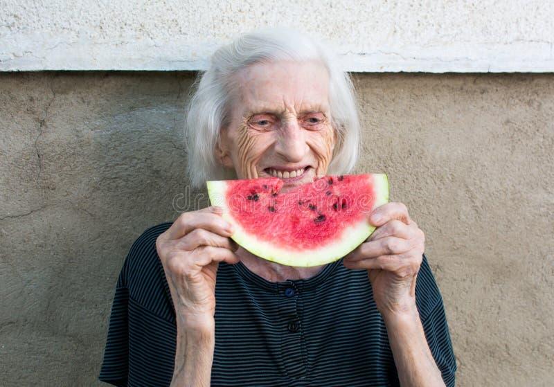 Rozochocony babci łasowania arbuz w podwórku zdjęcia royalty free