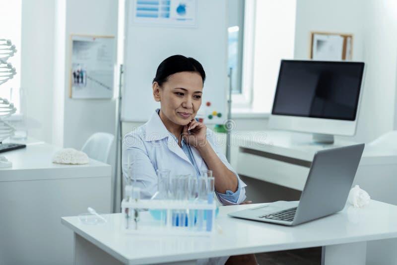 Rozochocony badacz pracuje na jej laptopie w lab zdjęcie stock