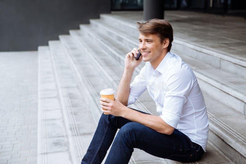 Rozochocony biznesmen opowiada na telefonie komórkowym z filiżanką kawy obraz stock