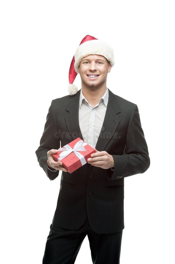 Rozochocony biznesmen w Santa mienia czerwieni kapeluszowym prezencie zdjęcie royalty free