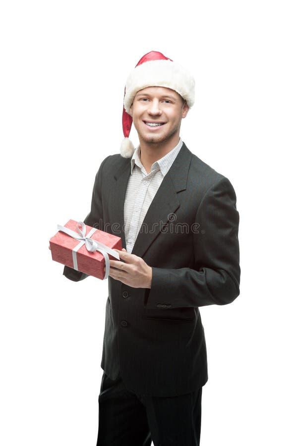 Rozochocony biznesmen w Santa mienia czerwieni kapeluszowym prezencie zdjęcia stock