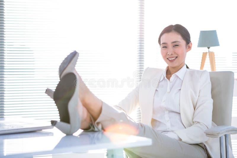 Rozochocony bizneswoman patrzeje kamerę z nogami na biurku obraz stock