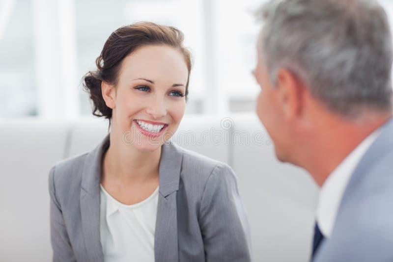 Rozochocony bizneswoman słucha jej workmate opowiadać zdjęcie stock