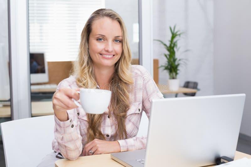 Rozochocony bizneswoman używa jej notatnika trzyma filiżankę zdjęcia royalty free