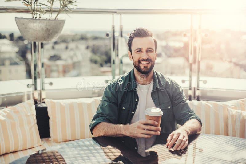 Rozochocony brodaty facet przy plenerową cukiernianą trzyma filiżanką kawy obrazy stock