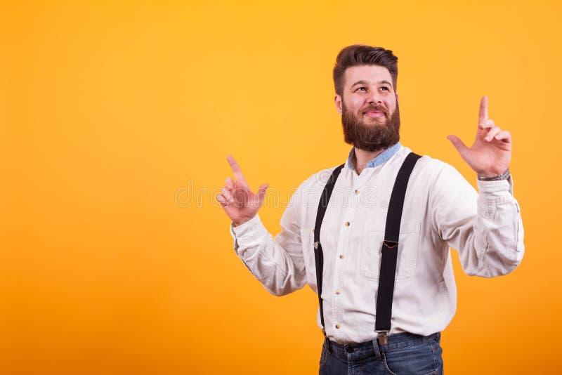 Rozochocony brodaty mężczyzna ono uśmiecha się i wskazuje w górę nadmiernego żółtego tła zdjęcie royalty free