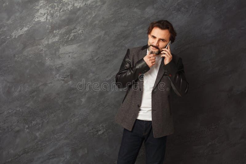 Rozochocony brodaty mężczyzna opowiada na telefonie fotografia royalty free