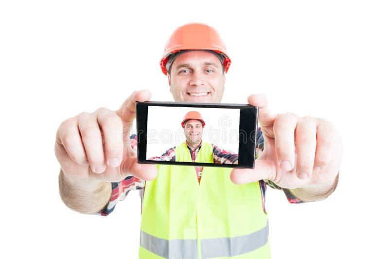 Rozochocony budowniczy używa telefon brać fotografię zdjęcie stock