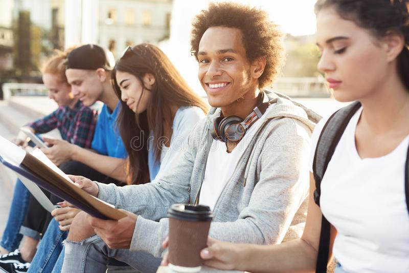 Rozochocony czarny studencki studiowanie plenerowy z groupmates zdjęcia stock