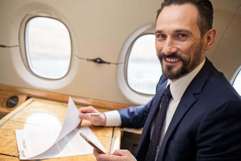 Rozochocony dyplomata pracuje na samolot desce obraz stock
