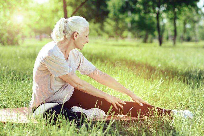 Rozochocony emeryt wolno ćwiczy w parku obrazy stock