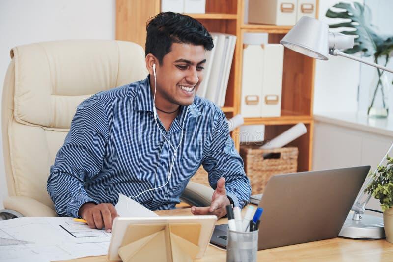 Rozochocony etniczny mężczyzna komunikuje z laptopem zdjęcie royalty free