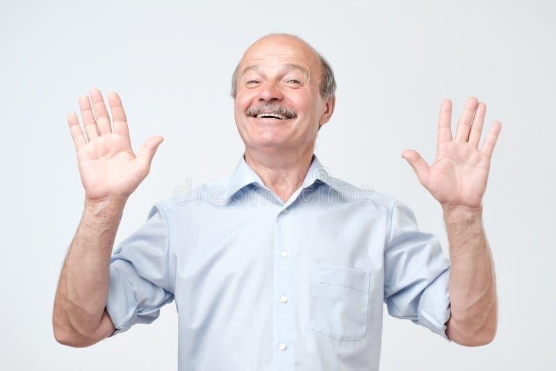 Rozochocony facet podnosi ręki jak przedstawienia jest uninvolved, szczęśliwego spojrzenie obrazy royalty free